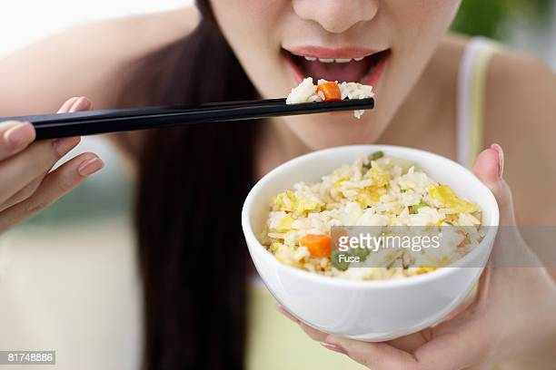 Young Woman Eating Rice Dish