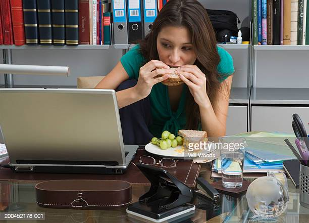 Young woman eating sandwich at desk