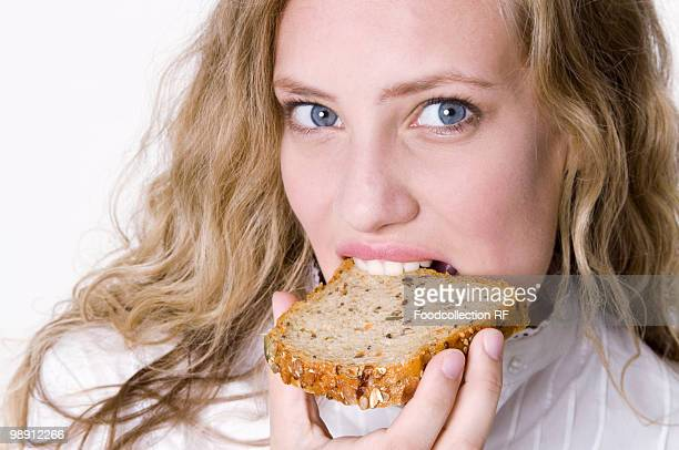 Young woman eating slice of granary bread, close-up