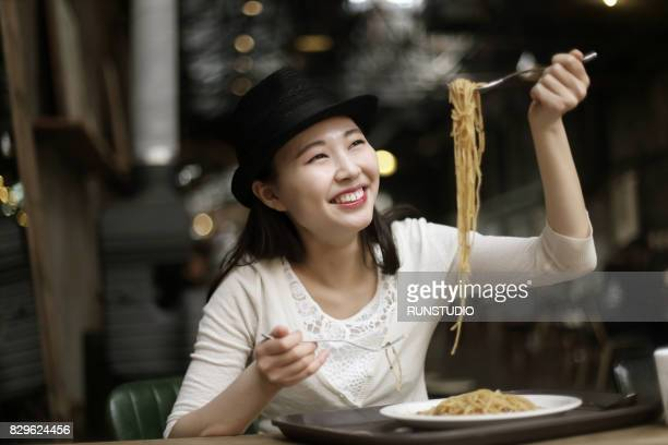 Young woman eating spaghetti in restaurant