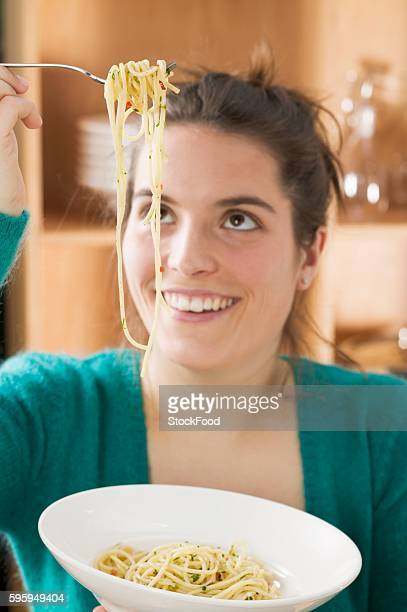 Young woman eating spaghetti with chillies