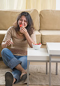 Young woman eating strawberries on living room floor