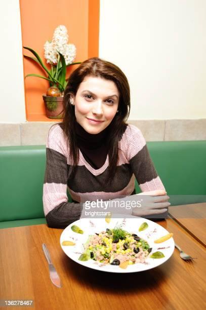 Jeune femme manger salade de thon
