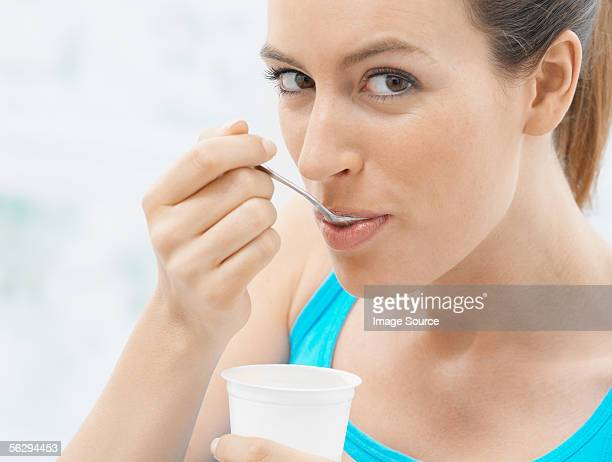 Young woman eating yoghurt