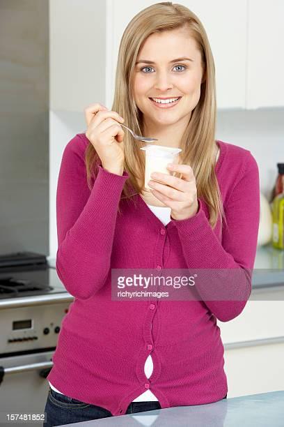 Jeune femme manger un yaourt