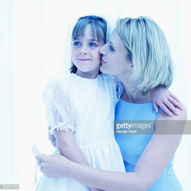 Young woman embracing a girl (11-13) wearing her first holy communion dress