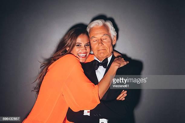 Young woman embracing elegant senior man