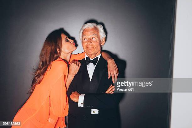 Young woman embracing elegant senior man