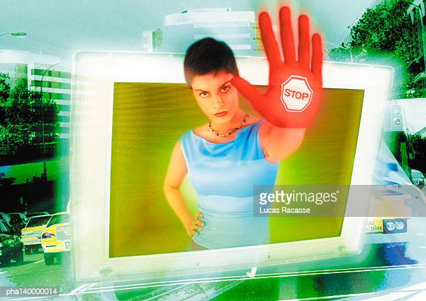 Young woman emerging from computer monitor, hand toward camera, the word stop on hand, digital composite.