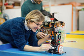 Young attractive woman engineer working on robotics project