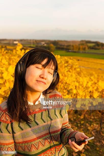 Young woman enjoy music in vineyard Switzerland