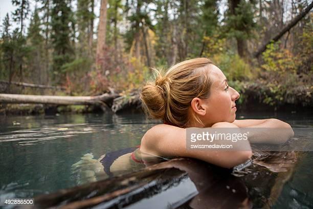 Young woman enjoying a natural bath at the hot springs.