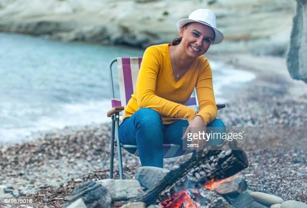 Joven disfrutando de la fogata en la playa