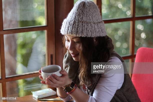 Young woman enjoying coffee in cafe