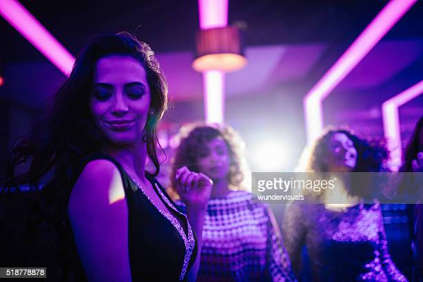 Young woman enjoying dancing with friends in a night club