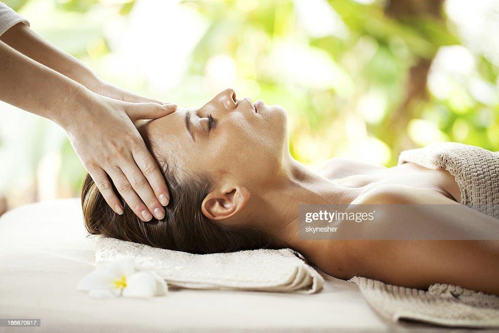 Young woman enjoying during head massage at tropical spa resort.
