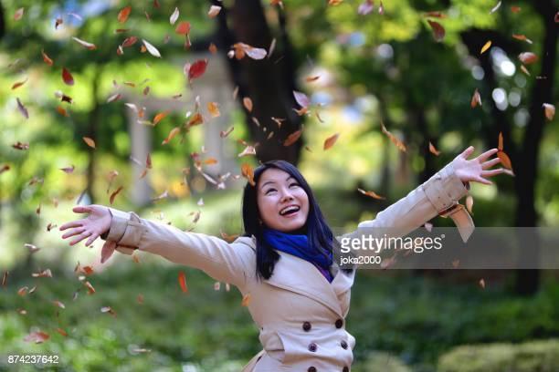 落ち葉のシャワーを楽しむ若い女性