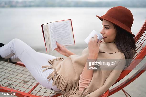 Junge Frau, die in ein Buch und warmen Getränk im Freien.