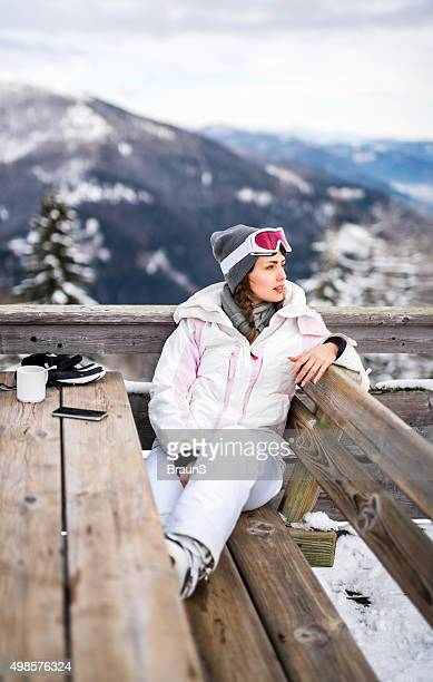 Young woman enjoying in a cafe at ski resort.