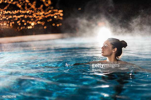 Young woman enjoying in a heated swimming pool at night.