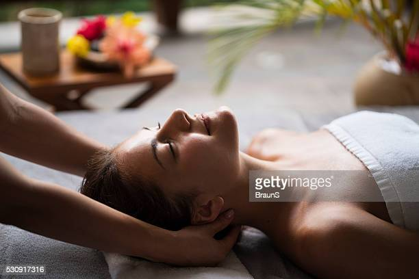 Young woman enjoying in a neck massage at the spa.