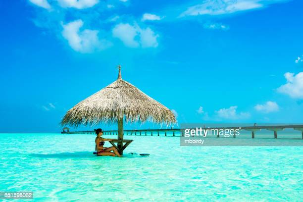 Young woman enjoying in sunshade at Dhiffushi Holiday island, South Ari atoll, Maldives
