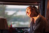 young woman enjoying morning sun next to her window