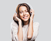 Happy young woman wearing headphones listening to the music
