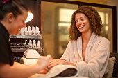 Young woman enjoying nail manicure in spa