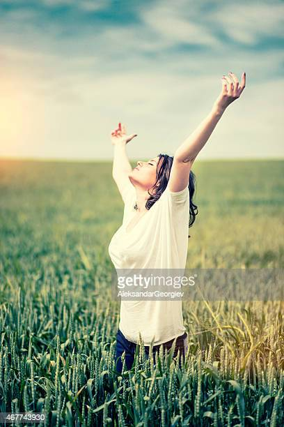 Young Woman Enjoying Nature with Spread Arms at Sunset