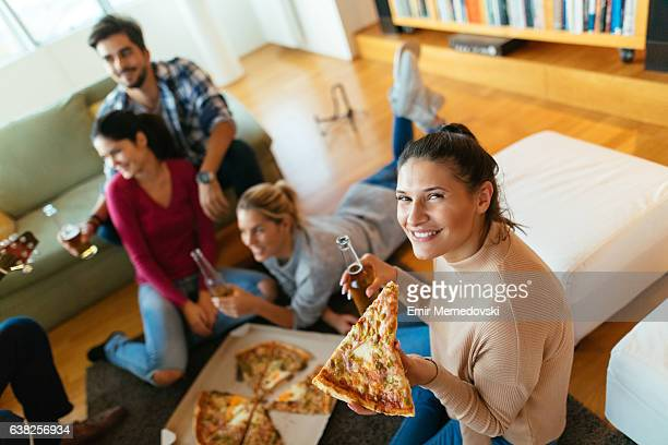Young woman enjoying pizza and beer at the party