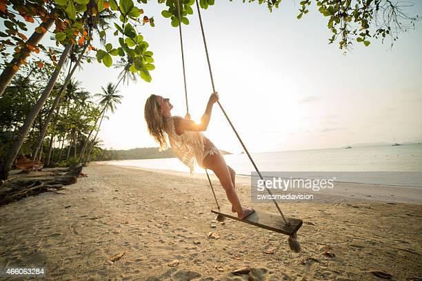 Junge Frau genießen seasaw am Strand bei Sonnenuntergang