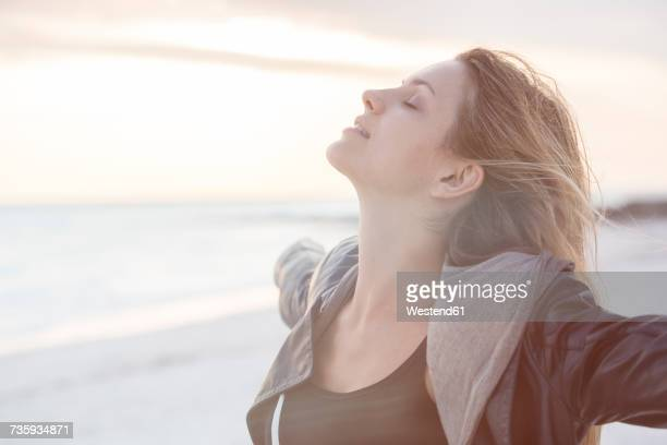 Young woman enjoying the beach at sunset