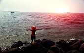 Young woman of Indian ethnicity wearing red color top and blue jeans also wearing red hat she standing on rock and enjoying fresh air near the seashore during sunset time, freedom concept.