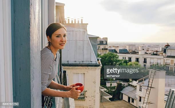 Jeune femme appréciant la vue depuis un appartement parisien
