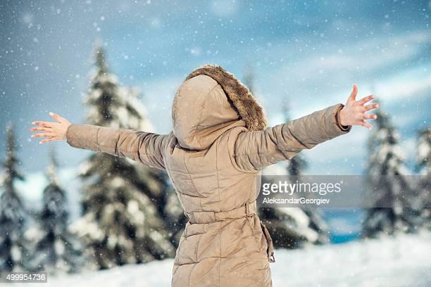 Giovane donna godendo inverno con le braccia sollevata mentre nevichi