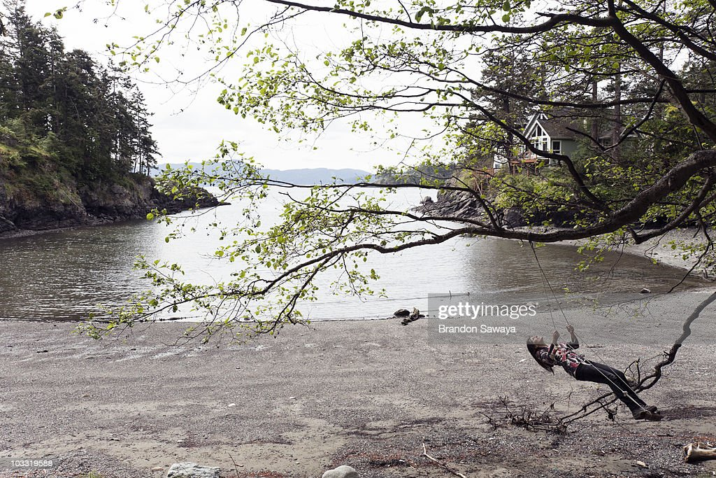 A young woman enjoys a swing hung from a tree near the water's edge of Doe Bay on Orcas Island.