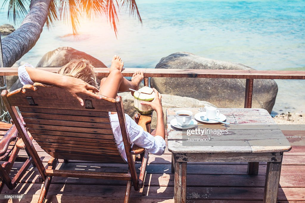 Young woman enjoys drinking coffee and coconut : Stock Photo