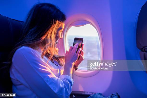 Young woman enjoys sunset from airplane window