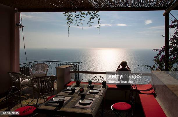 A young woman enjoys the expansive view of the Mediterranean Sea from a clifftop terrace of a restaurant pictured on October 31 2013 in Praiano Italy