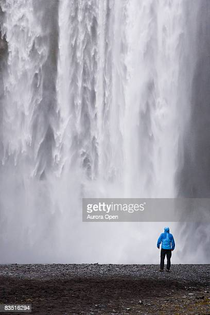 A young woman enjoys the view of Seljalandsfoss Waterfall in Iceland.