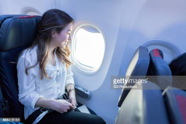 Young woman enjoys view from aircraft window seat