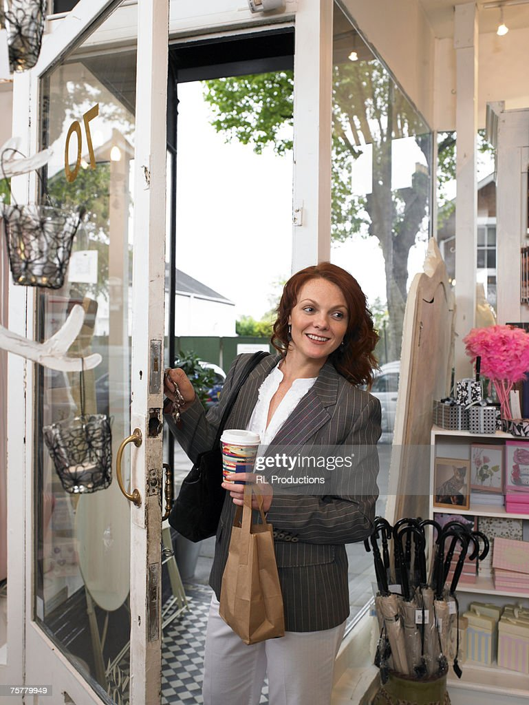 Young woman entering gift shop, smiling : Stock Photo