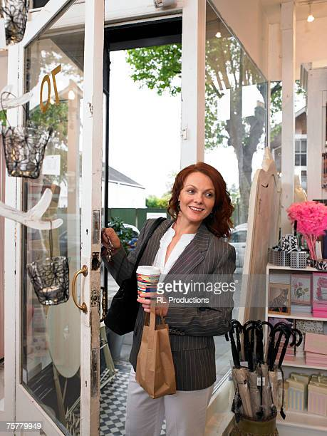 Young woman entering gift shop, smiling