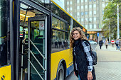 Young woman stepping into the bus