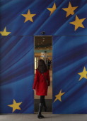 A young woman enters the glass doors decorated as the flag of the European Union at an entrance to the Berlaymont building of the European Commission...