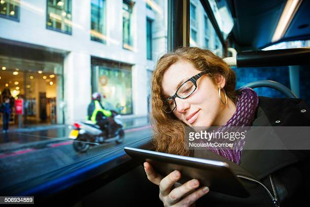 Young woman entertained by her tablet on a London bus