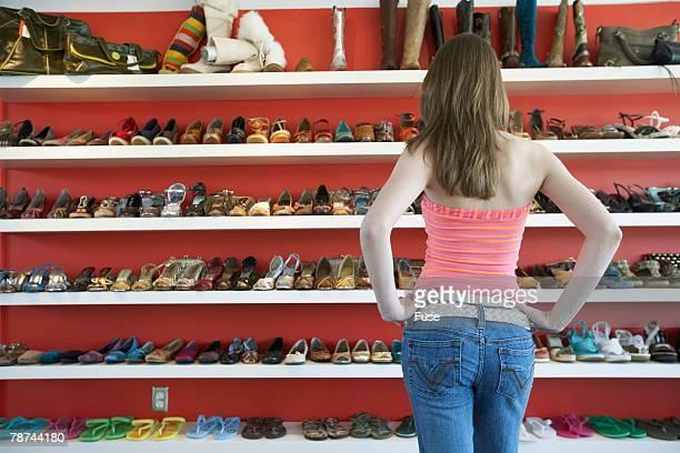 Young Woman Examining Shoe Rack