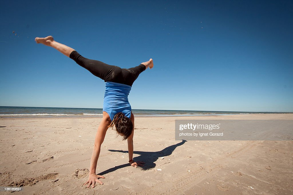 Young woman exercises on beach : Stock Photo