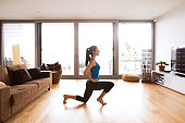 Beautiful young woman working out at home in living room, doing yoga or pilates exercise, stretching legs.